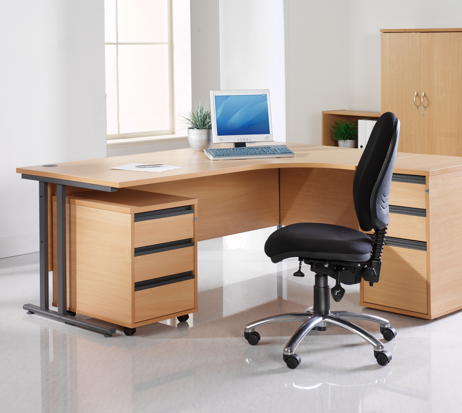 Desk with computer on it and a black swivel chair